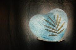 Bleu de papier de coeur de lampe avec la feuille sèche dessus dans l'obscurité Photographie stock