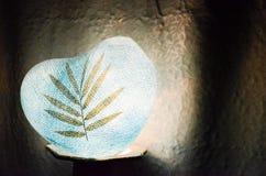 Bleu de papier de coeur de lampe avec la feuille sèche dessus dans l'obscurité Photo libre de droits