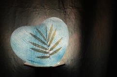 Bleu de papier de coeur de lampe avec la feuille sèche dessus dans l'obscurité Images libres de droits