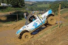 Bleu et blanc outre de la voiture de route tire dans la boue profonde Images libres de droits