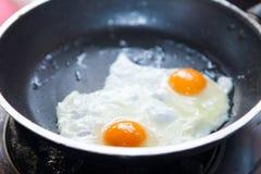 Bliźniacy smażący jajka na niecce Fotografia Stock