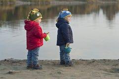 Bliźniacy stoją blisko jeziora z wiadrami Zdjęcie Royalty Free