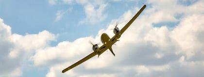 Bliźniaczy parowozowy tłokowy samolot podczas zwrota z wysokim bankiem na chmurnym, pogodnym niebie, obraz stock