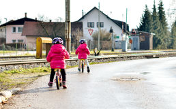 Bliźniaków dzieci jedzie równowagę jechać na rowerze na drodze z hełmem zdjęcie stock