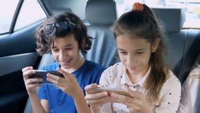 Bliźniaka brat i siostrzany używamy telefon w samochodzie podczas gdy podróżujący zbiory