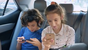 Bliźniaka brat i siostrzany używamy telefon w samochodzie podczas gdy podróżujący zbiory wideo