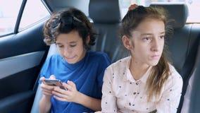 Bliźniaka brat i siostrzany używamy telefon w samochodzie podczas gdy podróżujący zdjęcie wideo