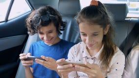 Bliźniaka brat i siostrzany używamy telefon w samochodzie podczas gdy podróżujący zdjęcie stock