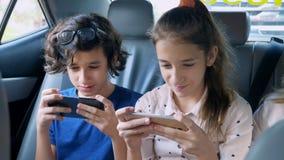 Bliźniaka brat i siostrzany używamy telefon w samochodzie podczas gdy podróżujący fotografia royalty free