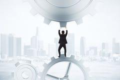 Bli det flytande begreppet med affärsmannen och kugghjul på stadsbackgroun Royaltyfri Foto