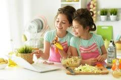 Bliźniacze siostry gotuje w kuchni Obraz Royalty Free
