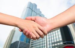 Bli partner med handen mellan en man och en kvinna på byggnadsbakgrund Fotografering för Bildbyråer