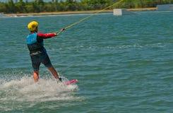 Bli Bli, Qld Australia, Marzec, - 16, 2018: Młody męski nastolatek jedzie wakeboard przy kablowym kilwateru parkiem Fotografia Stock