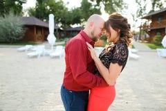 Bli skallig den caucasian maken som bär den röda skjortan och dansar med frun på trädgård Royaltyfria Foton