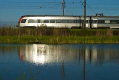 Blick在从银一列移动的火车的水中  免版税库存图片