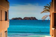 Blick aufs blaue Meer im Vordergrund ein Haus俯视的Th 免版税库存图片