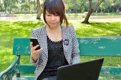 Blick der jungen Frau auf Handy mit Laptop Stockfotos