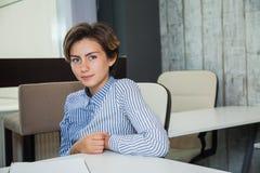 Blick der jungen Frau auf Kamera, Studentin sitzen im hellen Klassenzimmer Lizenzfreie Stockbilder