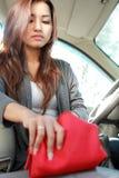 Blick der jungen Frau in etwas in ihrer roten Tasche Lizenzfreie Stockfotografie