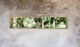 Blick des Gartens durch Abstand in der Betonmauer Lizenzfreie Stockfotos