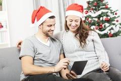 Blick des glücklichen Paars auf Tabletten-PC für Weihnachten Lizenzfreie Stockfotografie