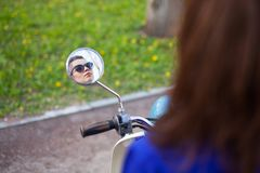 Blick des jungen Mädchens im runden Spiegel des Rollers Lizenzfreie Stockfotografie
