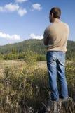 Blick des jungen Mannes auf die Berge Stockbild
