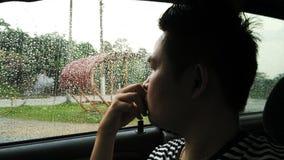 Blick des jungen Mannes auf die Tröpfchen auf Fenster Stockbild