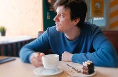 Blick des jungen Mannes auf Fenstergetränk ein Tee und essen ein Stück des Kuchens Lizenzfreie Stockfotos