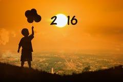 Blick des kleinen Jungen auf neues Jahr 2016 des Sonnenuntergangs Stockfotografie