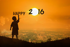 Blick des kleinen Jungen auf neues Jahr 2016 des Sonnenuntergangs Lizenzfreie Stockfotos