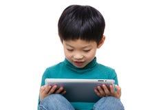 Blick des kleinen Jungen auf Tablette Lizenzfreie Stockfotografie