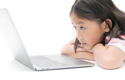 Blick des kleinen Mädchens auf den Monitorlaptop lokalisiert Stockfotos