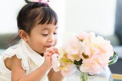 Blick des kleinen Mädchens auf die Blume Stockfoto