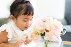 Blick des kleinen Mädchens auf eingemachte Blume Lizenzfreies Stockfoto
