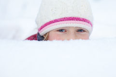 Blick des kleinen Mädchens aus Schneewehe mit smiley heraus mustert Stockfotografie