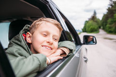 Blick des träumenden Jungen heraus vom Autofenster Lizenzfreie Stockbilder