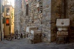 Blick eines Gebäudes mit herausgestellten Ziegelsteinen, alten Marmorbehältern und einem Fahrrad Lizenzfreies Stockbild