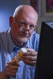 Blick för äldre man på kameran och fylla påreceptet direktanslutet, lodlinje Royaltyfri Foto