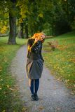 Blick junger Dame heraus durch Bündel Blätter Lizenzfreie Stockbilder
