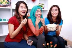 Blick mit drei jungen Frauen aufgeregt, wenn ein Film aufgepasst wird Lizenzfreie Stockbilder
