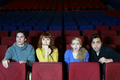 Blick mit vier Freunden auf Schirm im Kinotheater Lizenzfreie Stockfotos