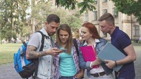Blick mit vier Studenten auf Smartphoneschirm auf dem Campus stockfotografie