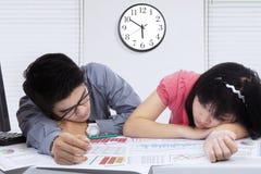 Blick mit zwei Arbeitskräften ermüdet mit Schreibarbeit Stockbild