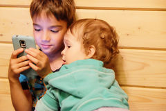 Blick mit zwei Brüdern zum Smartphone Stockbilder