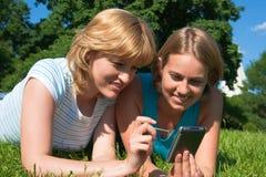 Blick mit zwei Frauen im Taschencomputer Lizenzfreie Stockfotografie
