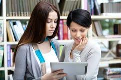 Blick mit zwei Freundinnen auf die Tablette Stockbilder