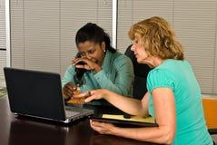 Blick mit zwei Geschäftsfrauen auf eine Laptop-Computer Stockbild