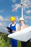 Blick mit zwei Ingenieuren auf Bauplan von Sonnenkollektoren Lizenzfreie Stockbilder