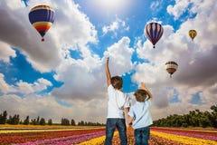 Blick mit zwei Jungen auf die Fliegenballone Stockfoto